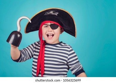 smiling boy dressed as a pirate on blue background