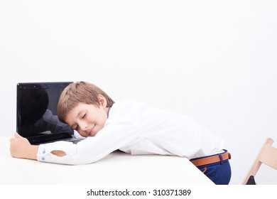 The smiling boy embracing his laptop computer on white background.