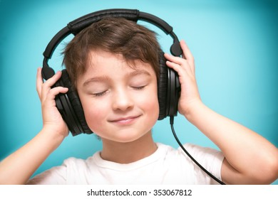Smiling boy with eyes closed listening to music on headphones