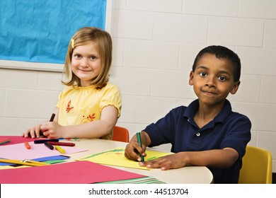 Smiling boy and girl doing projects in art class. Horizontally framed shot.