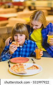 smiling boy and girl eating pizza or drinking juice indoor