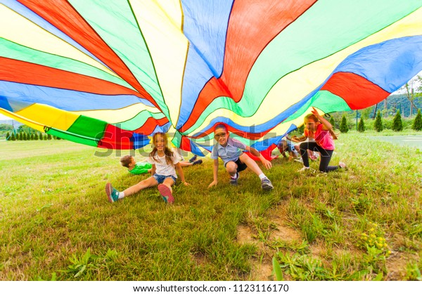 Smiling boy and girl under colorful parachute