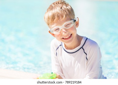 smiling boy in goggles by the pool enjoying summer vacation