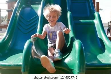 Smiling boy going down a slide with his hair raised due to static electricity