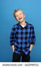 Smiling boy, happy child. Happy, smiling boy on a blue background expresses emotions through gestures.
