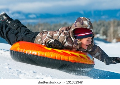 A smiling boy having fun sledding on a tube in the snow.