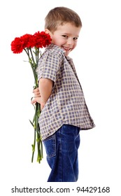 Smiling boy hiding a bouquet of red carnations behind itself, isolated on white