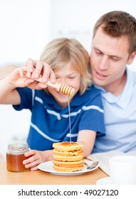 Smiling boy and his father putting honey on waffles in the kitchen
