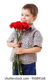 Smiling boy holding a bouquet of red carnations, isolated on white