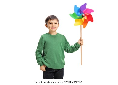 Smiling boy holding a colorful windmill toy isolated on white background
