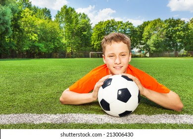 Smiling boy holding football with both arms