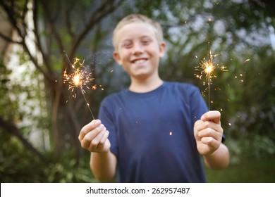 Smiling boy holding sparklers.  Focus on sparklers.
