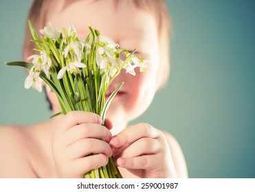 smiling boy holding spring flowers