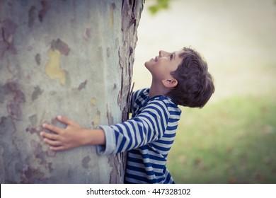 Smiling boy hugging tree trunk in park