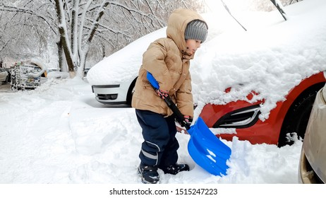 Smiling boy in jacket and hat helping to clean up the snow covered car after blizzard using big blue shovel