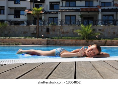 Smiling boy lies on the edge of swimming pool.
