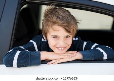Smiling boy looking out the car in a close up image
