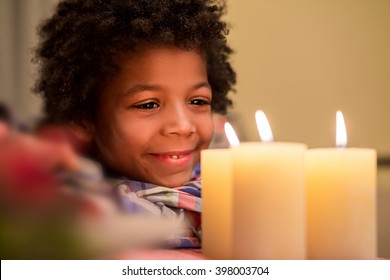 Smiling boy looks at candle. Happy kid beside Christmas candle. New Year shall bring happiness. Feel the holiday atmosphere.