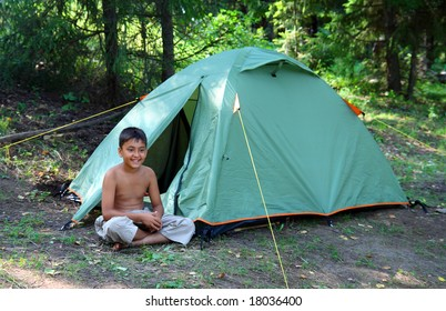 smiling boy near camping tent in forest