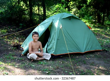 smiling boy near camping tent in summer forest