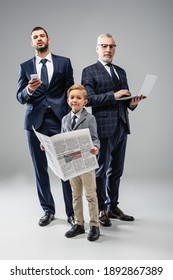 smiling boy with newspaper looking at camera near dad and grandfather holding gadgets on grey