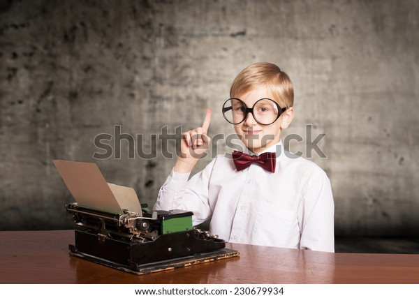 Smiling boy with the old typewriter raising the index finger up. Retro style portrait