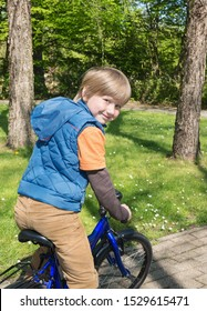 Smiling boy on a bicycle in a park