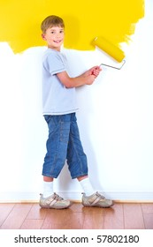 smiling boy painting interior wall of home.