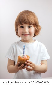 smiling boy red-haired boy in white shirt holding a cake. kids' beauty. children concept