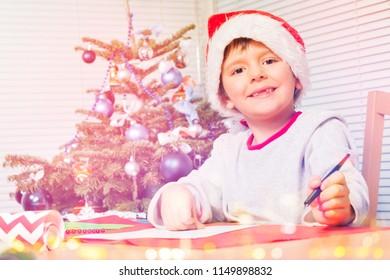 Smiling boy in Santa hat writing Christmas letter