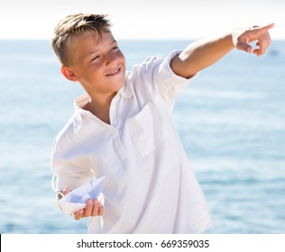 smiling boy showing with finger and standing on beach on sunny weather