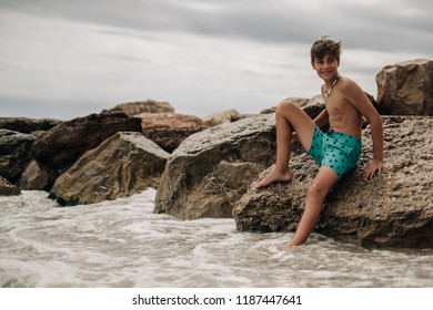 Smiling boy sitting on the beach rock with leg in the water