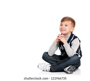 Smiling boy sitting on floor and looks into the distance isolated on white background