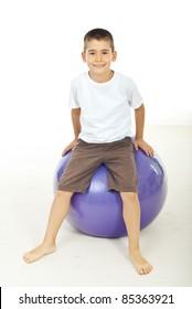 Smiling boy sitting on pilates ball barefoot