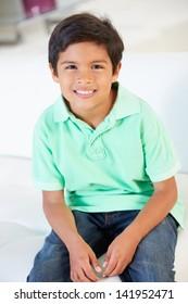 Smiling Boy Sitting On Sofa