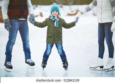 Smiling boy skating with parents