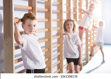 Smiling boy standing next to a stall bar in sport outfit during corrective gymnastics classes