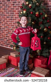 Smiling boy standing on the floor next to the presents and a tree