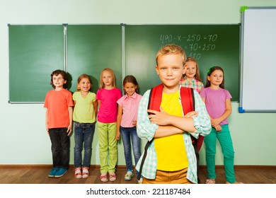 Smiling boy stands in front near blackboard