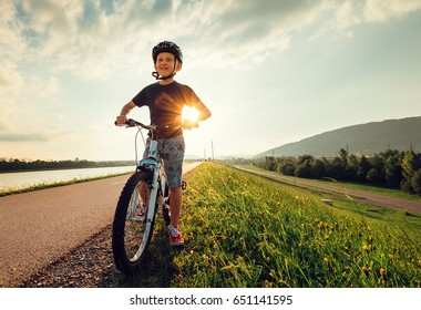 Smiling boy starts to ride a bicycle