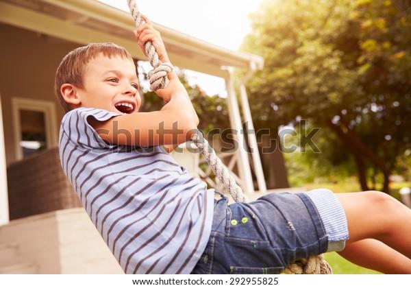 Lächelnder Junge, der auf einem Seil auf einem Spielplatz schwingt
