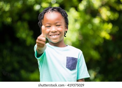 Smiling boy with thumbs up in the park
