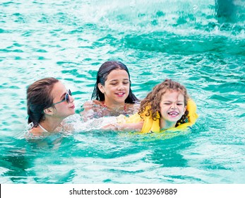 A smiling boy and two girls are swimming in a pool in a water park