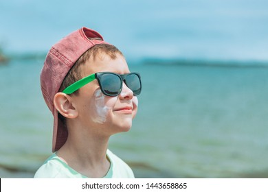 smiling boy wearing sunglasses and sunscreen on his face. copy space for your text