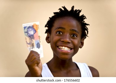 A smiling boy with a white sleeveless shirt holding money.