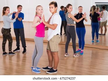 Smiling boys and girls dancing rumba in training