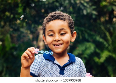 Niña brasileña sonriente jugando con burbujas de jabón en el jardín. Chico feliz. Estilo de vida. Día del Niño
