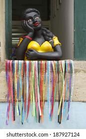 Smiling Brazilian woman colorful namoradeira figurine in the window decorated with wish ribbons fita do Bonfim Salvador Bahia Brazil