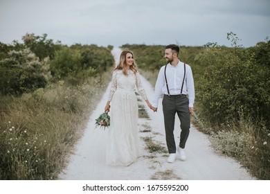 Lächeln Braut und Bräutigam verbringen Zeit zusammen. Posing auf dem Hintergrund der Berge. Dressen in weißem Kleid schöne blonde Kaukasische Braut und gut aussehende Bräutigam.