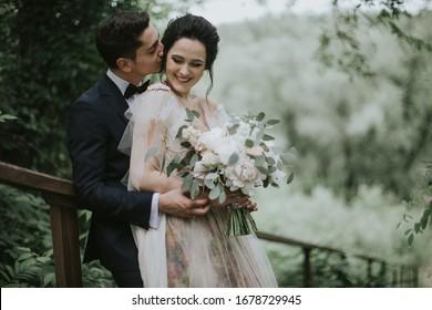 Lächeln Braut und Bräutigam verbringen Zeit zusammen. Posing auf dem Hintergrund der Berge. Dressen in weißem Kleid schöne blonde Kaukasische Braut und gut aussehende Bräutigam. Hugs, Küssen und genießen Sie die Gesellschaft
